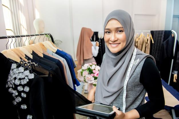 Asian muslim woman designer in her tailor shop Premium Photo