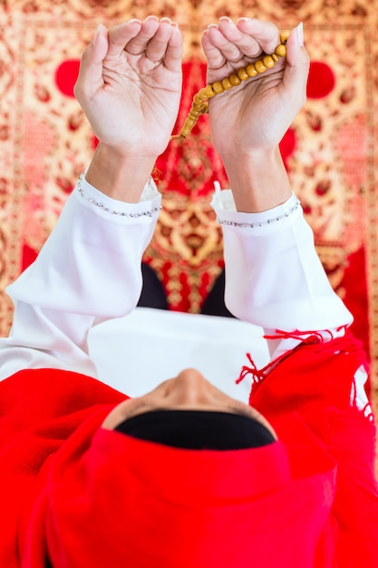 Asian muslim woman praying with beads chain Premium Photo