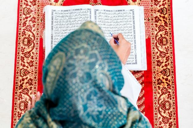Asian muslim woman studying koran or quran Premium Photo