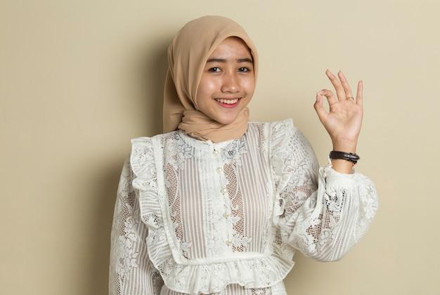 확인 표시 제스처와 Hijab를 입고 아시아 무슬림 여성 프리미엄 사진