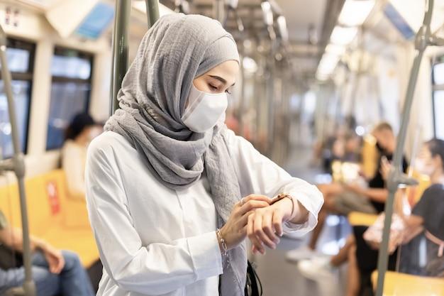 Азиатская мусульманская женщина нося медицинский лицевой щиток гермошлема для предотвращения пыли и вируса инфекции и смотря smartwatch в публике системы перехода skytrain. Premium Фотографии