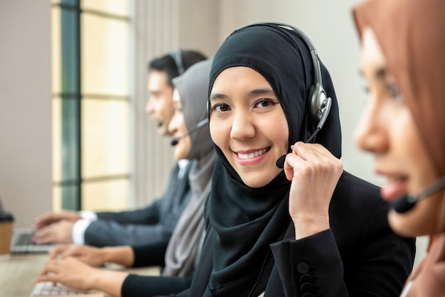 Asian muslim woman wearing microphone headsets working with team in call center Premium Photo