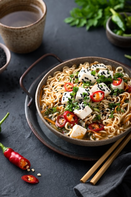 Asian noodle soup, ramen with tofu and vegetables in ceramic bowl on dark background, selective Premium Photo