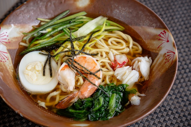 Asian noodle soup with crab meat, boiled egg, shrimp and spinach Premium Photo