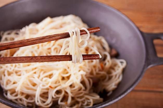 Asian noodles with beef, vegetables in wok with chopsticks, rustic wooden background. asian style dinner. chinese japanese noodles Premium Photo