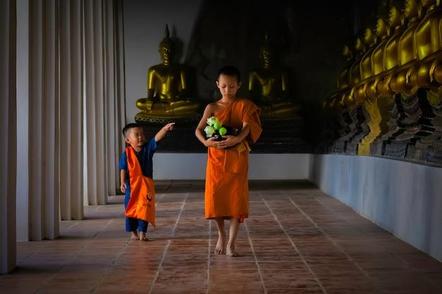 Asian novice monk walking in temple phutthaisawan at ayutthaya, thailand. Premium Photo