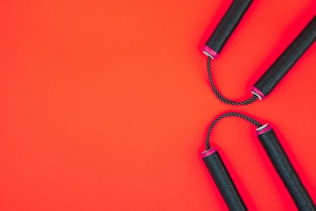 Азиатское оружие нунчаку на красной поверхности Premium Фотографии