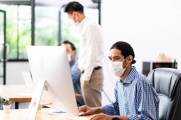 社会的距離の練習で新しい通常のオフィスで働く防護マスクを持つアジアのオフィスの従業員。コロナウイルスcovid-19の拡散を防ぎます。 Premium写真