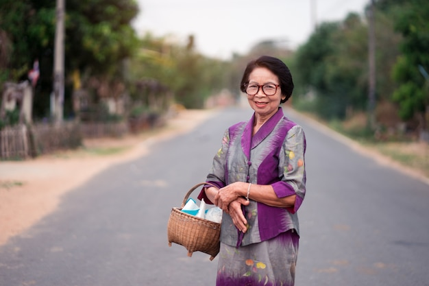Asian old women holding bamboo basket in countryside. Premium Photo
