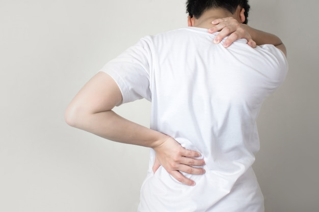 Asian people have shoulder pain to the back. using hands to hold on the shoulders and spines. Premium Photo