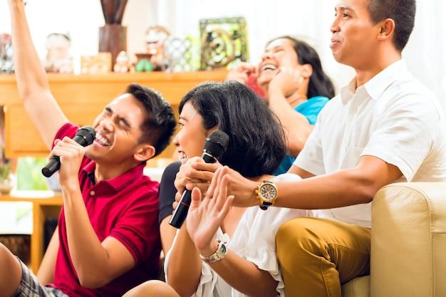 Asian people singing at karaoke party Premium Photo