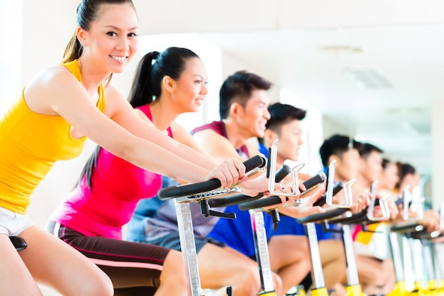 Asian people in spinning bike training at fitness gym Premium Photo