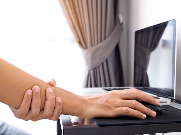 Азиатские люди, работающие с ноутбуком, испытывают боли в суставах и боли в области запястья и руки или симптомы офисного синдрома. Premium Фотографии