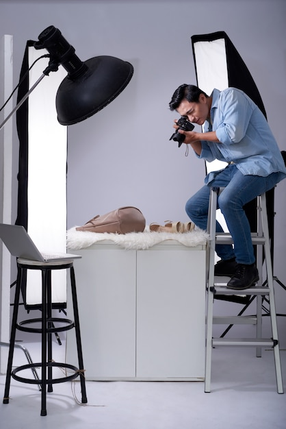 Asian photographer sitting on ladder in studio with camera and taking photos of fashion items Free Photo