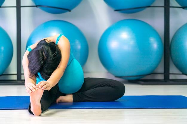 Asian pregnant woman doing yoga in gym Premium Photo