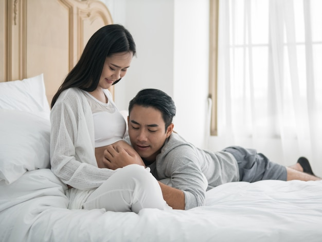 Asian pregnant woman and husband laying on the bed while spending time together Premium Photo