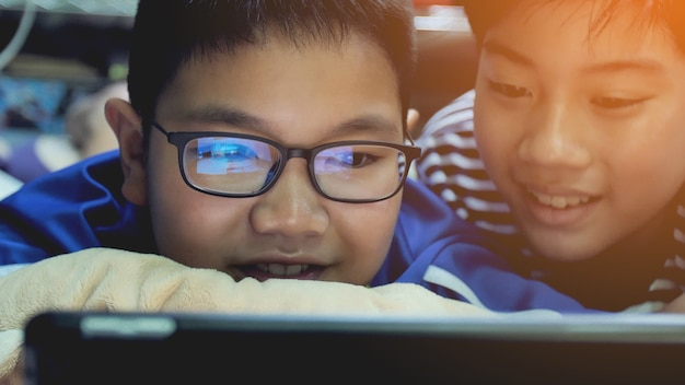 Asian preteens watching on tablet computer , smile face. Premium Photo