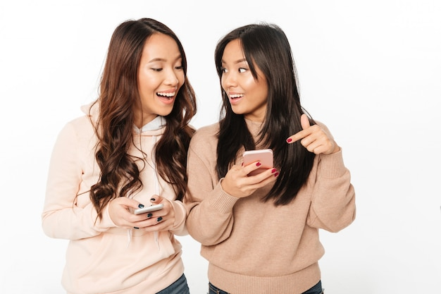 Asian pretty happy ladies sisters chatting by mobile phones. Free Photo