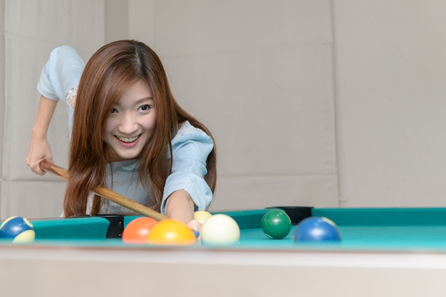 Asian pretty woman playing billards, Premium Photo