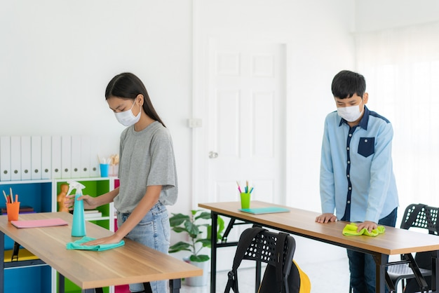 Asian primary student wearing masks and cleaning table by wipe and ...