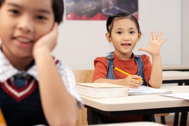 Asian pupils sitting in classroom and girl putting up hand to answer Free Photo