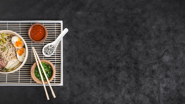 Asian ramen noodles with eggs and sauces on placemat Free Photo