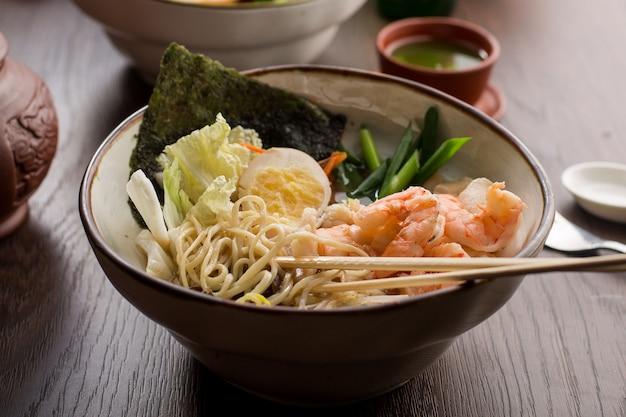 Азиатский рамен с креветками и лапшой в ресторане Premium Фотографии