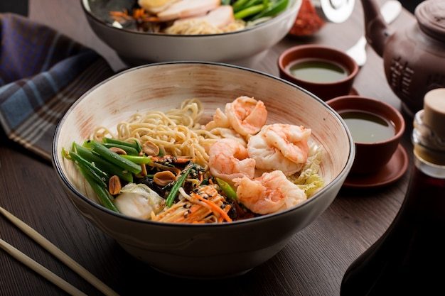 Asian ramen with shrimps and noodles in a restaurant Premium Photo