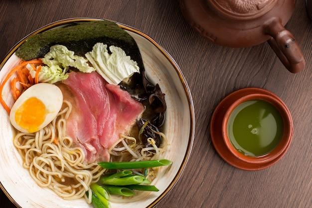 Азиатский рамен с тунцом, лапшой и чаем в ресторане Premium Фотографии