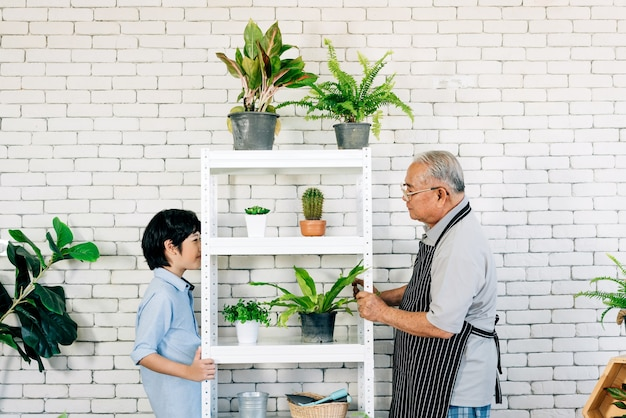 Asian retirement grandfather and his grandson with smiles, spending quality time together by enjoy taking care of plants in an indoor garden. family bonding between old and young. Premium Photo