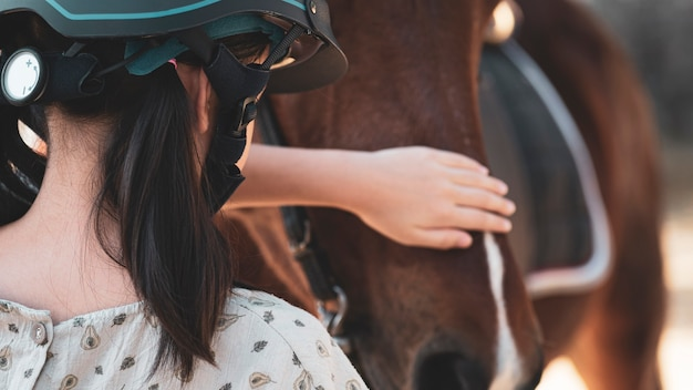 Asian school kid girl with horse ,riding or practicing horse ridding at horse ranch. Premium Photo