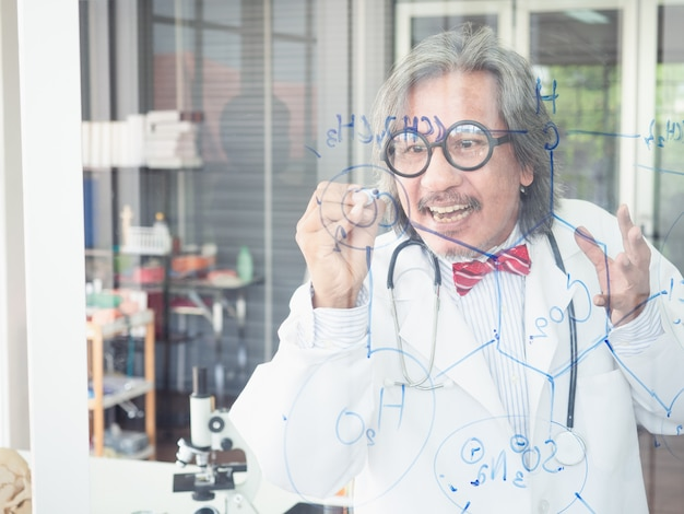 Asian scientist writes a formula on a glass board Premium Photo