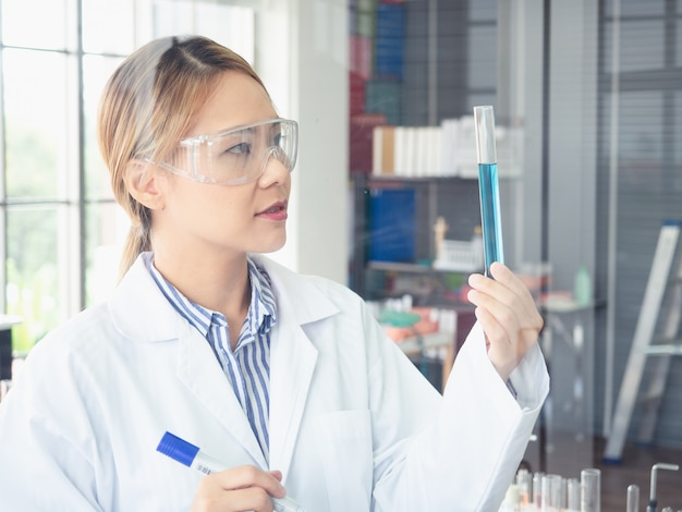 Asian scientist writes a formula on a glass board Premium Photo