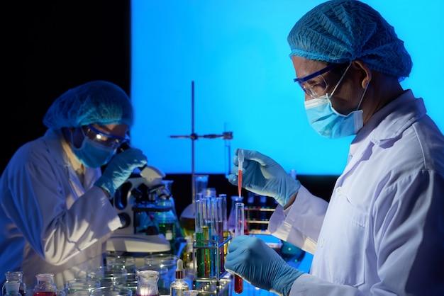 백신 제작에 종사하는 아시아 과학자 무료 사진
