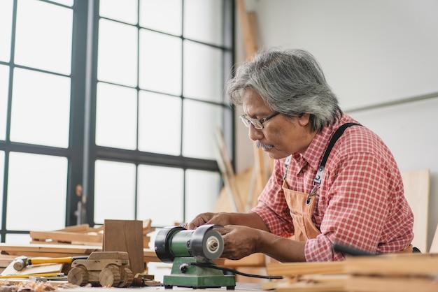 Asian senior carpenter man using small grinder machine make wooden car at workshop Premium Photo