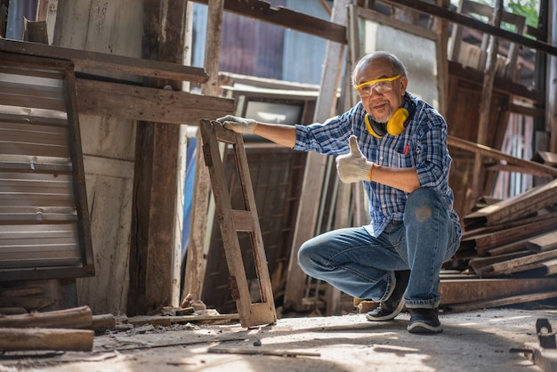 Asian senior carpenter show thumbs up old window frames for renovating at the carpentry workshop Premium Photo