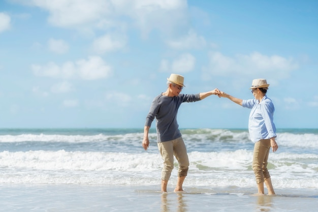 Asian senior couple dancing on the beach.elderly honeymoon together very happiness after retirement.plan life insurance.activity after retirement on summertime Premium Photo