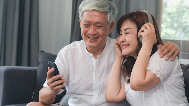 Asian senior couple relax at home. asian senior chinese grandparents, husband and wife happy wear headphone using mobile phone listen to music while lying on sofa in living room at home concept. Free Photo