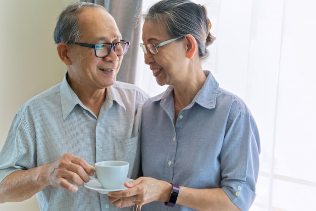 Asian senior couple smiling and looking on each other. Premium Photo