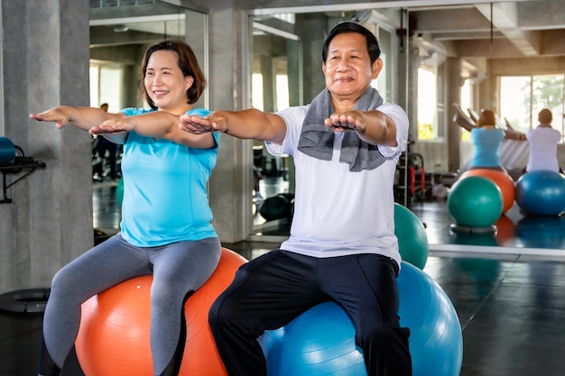 Premium Photo | Asian senior couple smiling in sportswear exercising at gym.