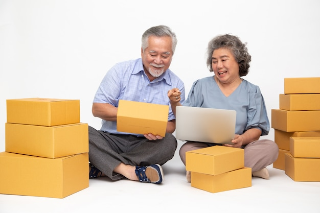 Asian senior couple startup small business freelance with parcel box and computer laptop and sitting on floor isolated on white wall, online marketing packing box delivery concept Premium Photo