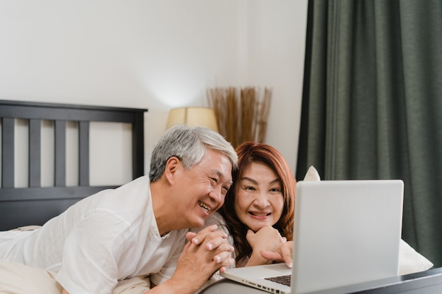 Asian senior couple using laptop at home. asian senior chinese grandparents, husband and wife happy after wake up, watching movie lying on bed in bedroom at home in the morning concept. Free Photo