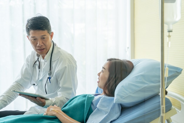 Asian senior doctor sitting on hospital bed and discussing with female patient Premium Photo