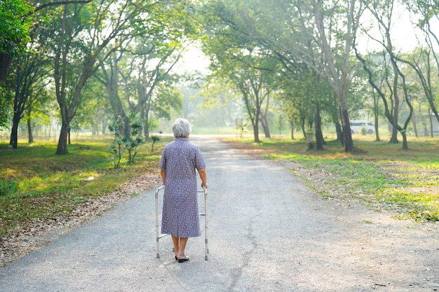 Asian senior or elderly old lady woman patient walk with walker in park Premium Photo