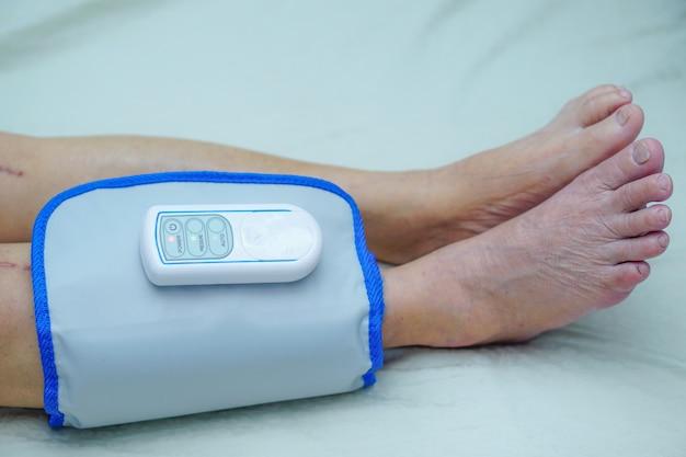 Asian senior or elderly old woman patient with cordless air compression pressure leg massa Premium Photo