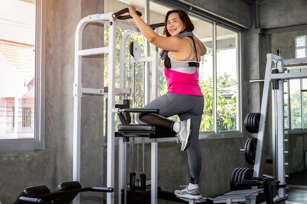 スポーツウエアトレーニングジムでマシンに戻ってでアジアのシニア脂肪女性。 Premium写真