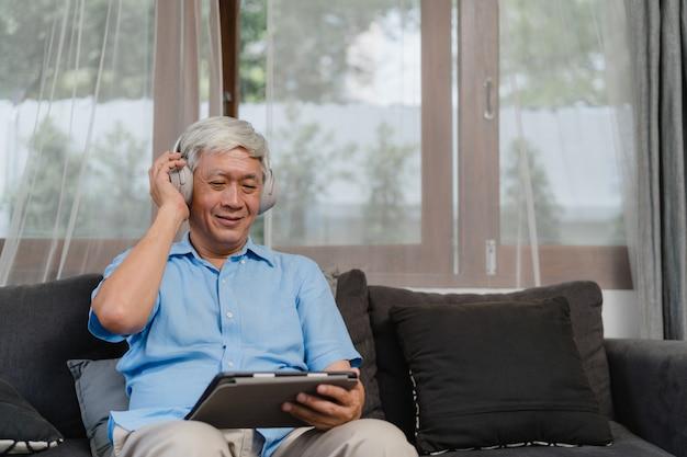 アジアの年配の男性は自宅でリラックスします。ホームコンセプトのリビングルームのソファに横たわっている間、タブレットのリスニングポッドキャストを使用してアジアの古い男性の幸せな着用ヘッドフォン。 無料写真