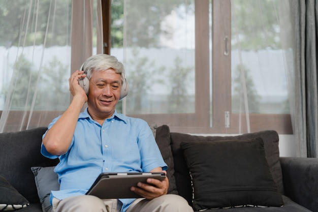 Asian senior man relax at home. asian older male happy wear headphone using tablet listening podcast while lying on sofa in living room at home concept. Free Photo