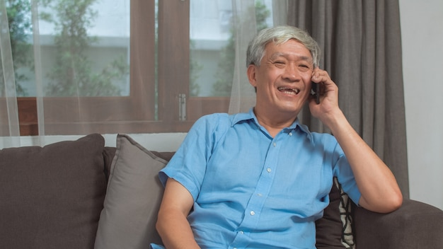Asian senior man talk on phone at home. asian senior older chinese male using mobile phone talking with family grandchild kids while lying on sofa in living room at home concept. Free Photo