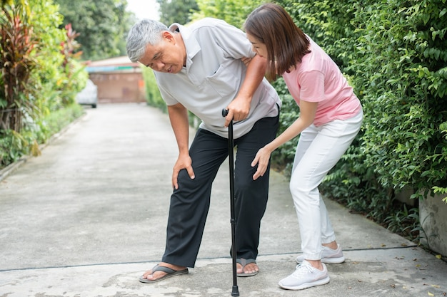 Азиатский пожилой мужчина гуляет на заднем дворе и болезненное воспаление и жесткость суставов артрит Premium Фотографии
